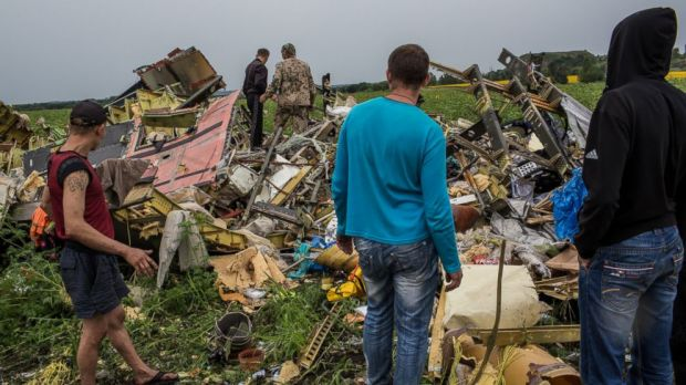 Plane parts are spread out over a wide area, consistent with it having been shot down.    Here people in Grabovka, Ukraine wander among crash remnants.